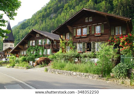MEIRINGEN, SWITZERLAND- JUNE 13, 2015: The ancient traditional chalet along the Kapellen. The town is well known for its location near the famous Reichenbach Falls.             - stock photo
