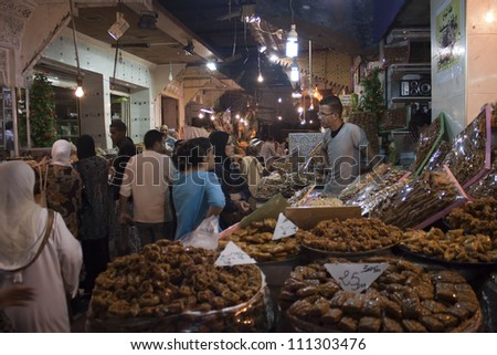 MEKNES - JUL 29: Vendors and customers stand by sweets stall at covered market in Meknes, Morocco on Jul 29, 2010. The market is one of the most important attractions of the city.
