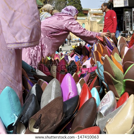 MEKNES, MOROCCO - APRIL 6: Unidentified women buy slippers, babouches, from a stall holder in the souk on April 6, 2011. These slippers have become popular in Europe
