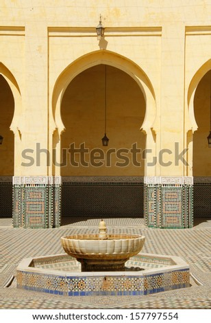 MEKNES, MOROCCO - AUGUST 24: Arabesque arch and fountain in the Moulay Ismail Mausoleum, the most important tourist icon in Meknes - UNESCO World Heritage. On August 24, 2013 in Meknes, Morocco.