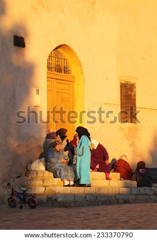 MEKNES, MOROCCO - DECEMBER 22: Group of typically dressed Moroccan women sitting on steps in the late afternoon winter sunshine. On December 22, 2013 in Meknes, Morocco. - stock photo
