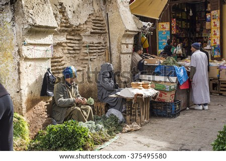 Meknes, Morocco - December 9, 2015: Man selling typical arabian aromatic herbs and a woman selling typical arabian bread (flatbread) in a tipycal street of Meknes medina. Meknes, Morocco. - stock photo