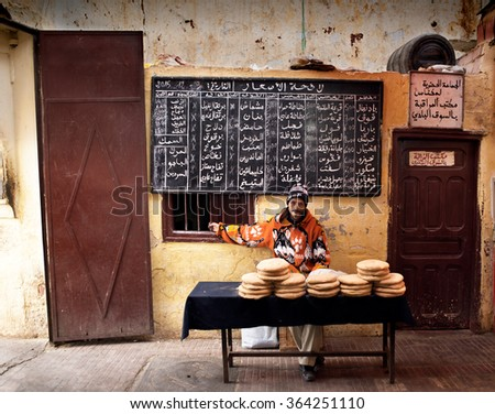 Meknes, Morocco - December 9, 2015: Man selling typical arabian bread (flatbread) in a traditional bakery in a market of Morocco. Meknes, Morocco. - stock photo