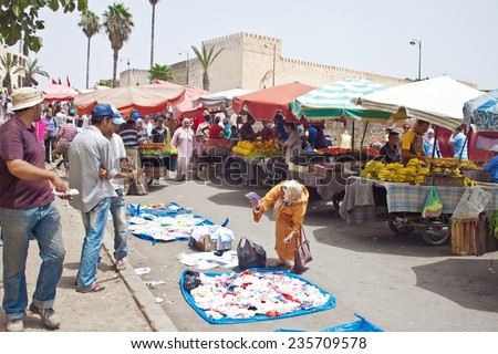MEKNES, MOROCCO - JULY 28: Arabic people at a market on July 28, 2010 in Meknes, Morocco. Meknes is a historic city listed in UNESCO and it has long tradition in handicrafts. - stock photo