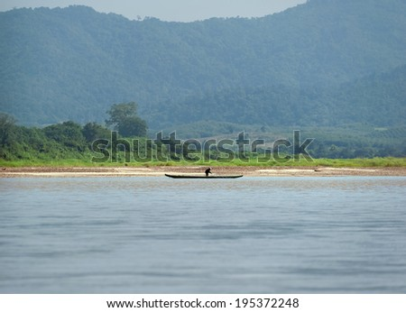 Mekong River Cruise in Laos. Popular tourist adventure trip by slow boat from Huay Xai to Luang Prabang. Fisherman on small boat against green mountains  - stock photo