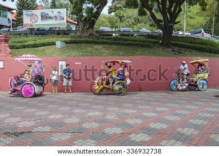 Melaka, Malaysia - August 2, 2015: Decorated trishaw with colorful flowers and doll for hire at Malacca city, Malaysia. - A popular historic tourist attraction and trishaw riding in Melaka, Malaysia.