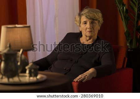 Melancholic senior lady relaxing alone in chair - stock photo