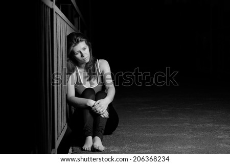 melancholy woman in a dark portrait - stock photo