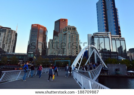 MELBOURNE,AUS - APR 14 2014:People pass on the Southbank Foot Bridge.It's a very popular bridge that crossing the Yarra River and connect the South Bank to Melbourne  CBD for pedestrians and cyclists.