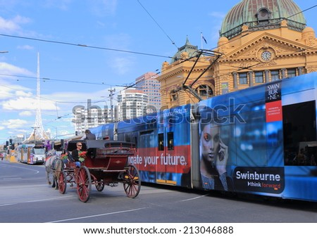 MELBOURNE AUSTRALIA - AUGUST 23, 2014: Tram passes horse carriage in front of Flinders Station - Melbourne was crowned the most liveable city 2013 in the Economist Intelligence Unit Survey.