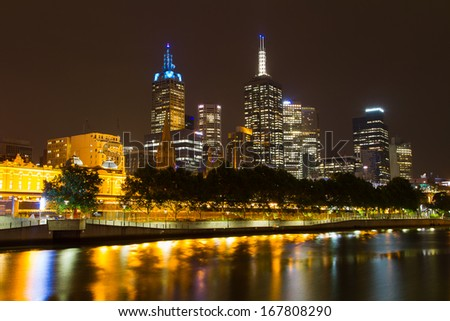 MELBOURNE, AUSTRALIA - DEC 03: Melbourne CBD night panorama with Flinders station from Yarra River at night on December 03, 2013, Melbourne, Australia. Lighting along Yarra makes recognizable views