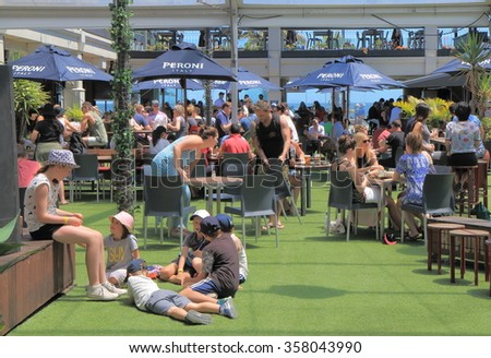 MELBOURNE AUSTRALIA - DECEMBER 29, 2015: Unidentified people dine in St Kilda beach in Melbourne. St Kilda is home to many attractions such as Luna Park and St Kilda beach.  - stock photo