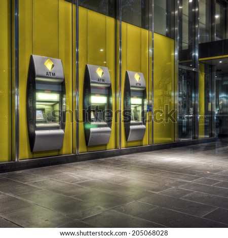 "Melbourne, Australia - February 19, 2012: A row of three Commonwealth Bank automatic teller machines in the CBD at night. The Commonwealth Bank is the largest of the ""big four"" Australian banks. - stock photo"