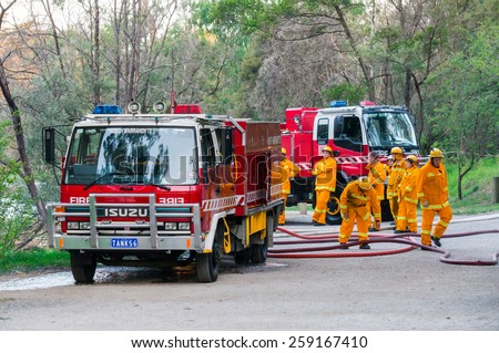 MELBOURNE, AUSTRALIA - February 10, 2015: Volunteer fire fighters from the North Warrandyte brigade of the Country Fire Authority practicing by the Yarra River in Warrandyte, with Isuzu fire trucks. - stock photo