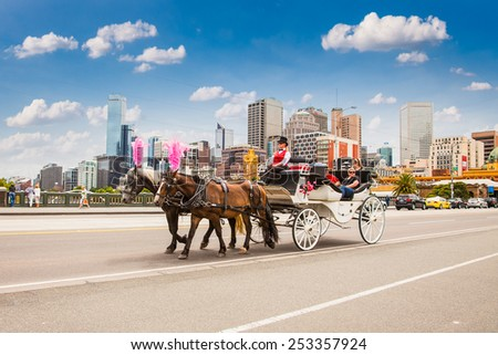 MELBOURNE, AUSTRALIA - JAN 15,2015: Coach with tourists crossing the bridge on Jan 15, 2015 in Melbourne, Australia. Horse carriage is a popular way for sightseeing in Melbourne. - stock photo