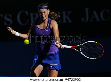 MELBOURNE, AUSTRALIA - JANUARY 26: Petra Kvitova of Czech Republic hits a return to Maria Sharapova of Russia during Australian Open tennis tournament, January 26, 2012 in Melbourne, Australia. - stock photo