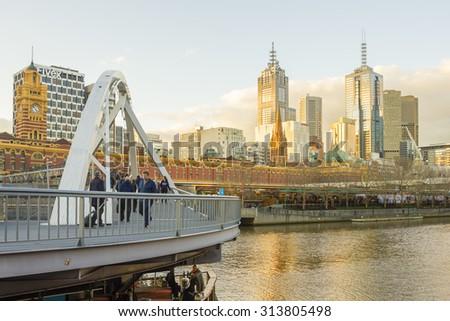 Melbourne, Australia - July 22, 2015: View of a footbridge and cityscape of Melbourne, Australia near sunset.  - stock photo