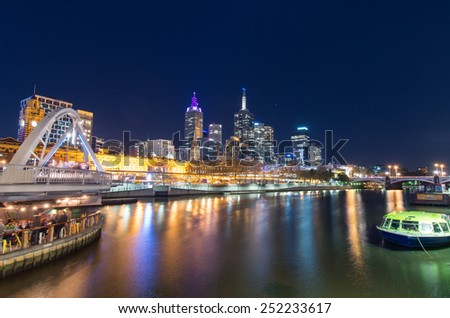 MELBOURNE, AUSTRALIA - June 8, 2014: night view of the Melbourne skyline, with the Southgate Footbridge on the left and Flinders Street Station in the centre.