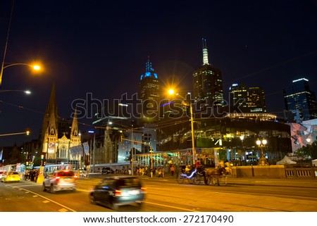MELBOURNE, AUSTRALIA - MARCH 21, 2015: Traffic on Flinders Street near thr Federation Square and Cathedral of Saint Paul at night.
