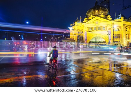 Melbourne, Australia - May 14, 2015: View of a crossroad outside Flinders Street Railway Station in downtown Melbourne, Australia at night - stock photo