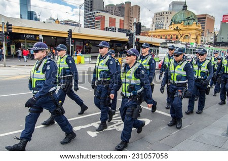 MELBOURNE, AUSTRALIA - November 16, 2014: Victoria Police officers marching in formation along Swanston Street, between Flinders Street Station and Federation Square.