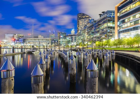 Melbourne, Australia - November 13, 2015: View of bollards, modern buildings, apartments and Etihad Stadium in Victoria Harbour Promenade in Docklands, Melbourne at night.  - stock photo