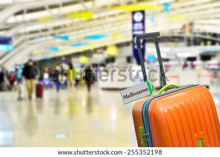 Melbourne, Australia. Orange suitcase with label at airport. - stock photo
