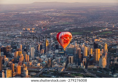 Melbourne, Australia - September 15, 2013: a hot air balloon floating above skyscrapers of central Melbourne at sunrise. - stock photo