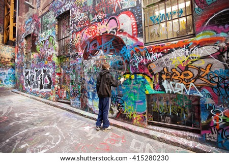 Melbourne, Australia-September 13, 2012. Graffiti artist in action in Hosier Lane, a much celebrated landmark mainly due to its sophisticated Urban art, in the centre of Melbourne, Victoria, australia - stock photo