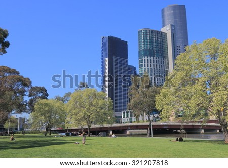 MELBOURNE AUSTRALIA - SEPTEMBER 26, 2015: Unidentified people relax at Batman Park. Crown Casino complex in background.