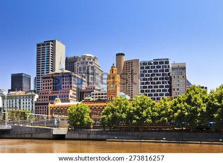 Melbourne city CBD cityline at Yarra river with greet trees and yellow river waters under blue sky