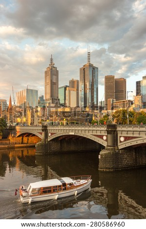 Melbourne City Skyline Cityscape and White Tour Boat Ferry cruise under Princes Bridge with Dramatic Golden Sky at Sunset in Summer Daytime, Australia - stock photo