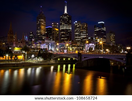 Melbourne Skyline with a reflection in the water of a couple standing on the bridge.
