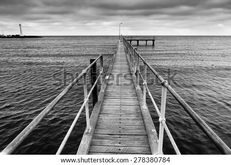 Melbourne St Kilda beach's wooden boardwalk towards open sea at sunset in black-white variant. No colour version, only BW - stock photo