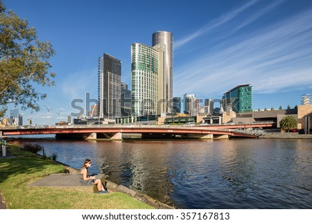 Melbourne, Victoria, Australia - Circa October 2015: An unidentified female sun bathing and reading alone Yarra river in-front of Crown Casino.