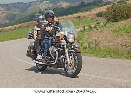 "MELDOLA, FC, ITALY - JULY 13: couple of bikers riding a vintage italian motorcycle Moto Guzzi California Classic at rally ""IX Moto Guzzi Memorial Zigolo"" on July 13, 2014 in Meldola, FC, Italy  - stock photo"