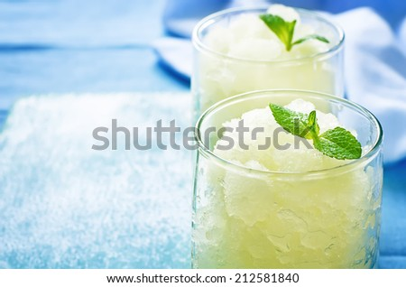 melon granita on light blue background. tinting. selective focus on mint - stock photo