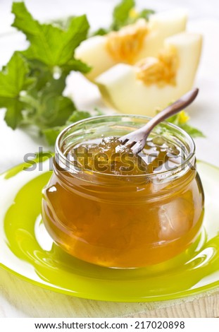 melon jam in a glass jar on a wooden background - stock photo