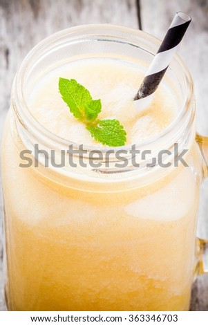 melon smoothie in a glass jar with mint and straw