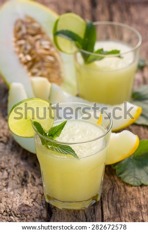 Melon smoothies with slices of melon on the wooden table