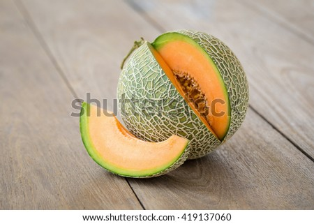 Melon with slices and on a wooden table.