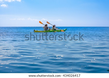 MELOS, GREECE - SEPTEMBER 4, 2012: Man and woman kayaking in calm Aegean Sea waters.