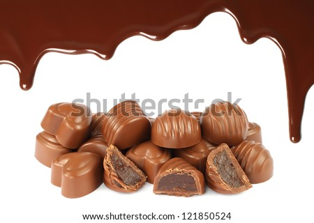 Melted chocolate dripping with candies on white background - stock photo