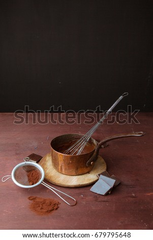 Melted chocolate in pan with whisk on the wooden background.