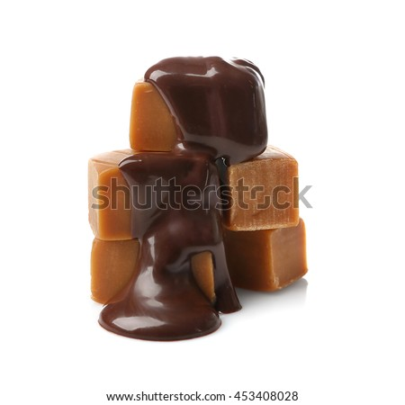 Melted chocolate with caramel candies, isolated on white - stock photo