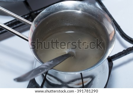 Melted gelatin in metal pot on the stove. Macro. Photo can be used as a whole background. - stock photo