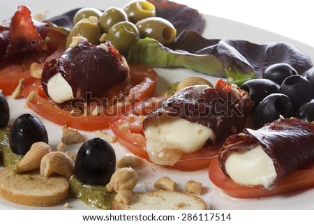 Melted mozzarella in beef prosciutto served on a white plate with tomatoes, olives and bruschetti.  - stock photo