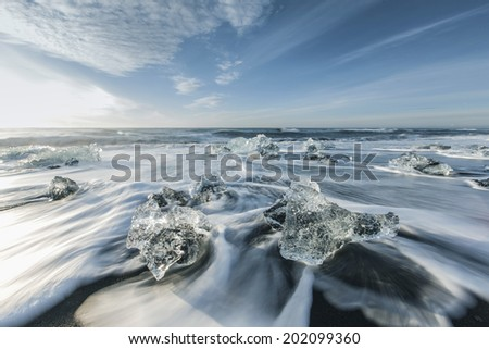 Melting ice on beach near Jokulsarlon in Iceland - stock photo