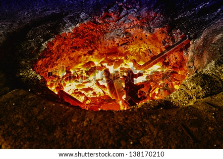 Melting iron pieces in a furnace hole - stock photo