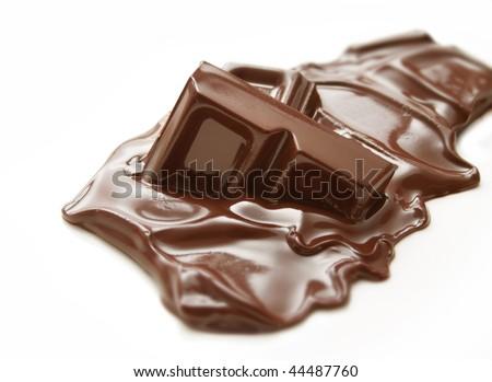 Melting piece of dark chocolate bar on white background - stock photo
